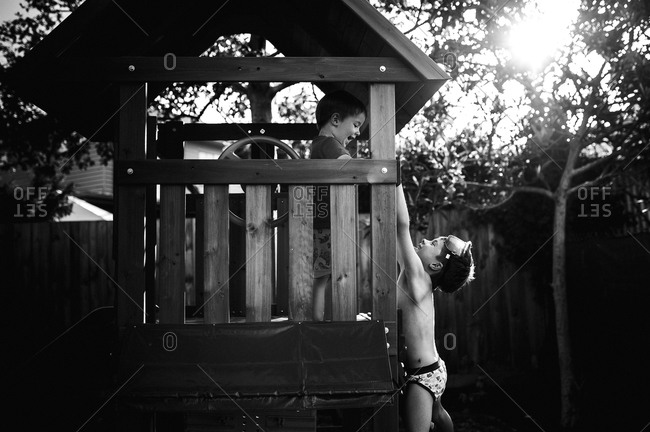 Brothers playing on a backyard play set