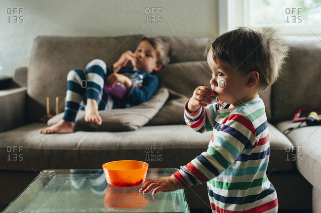 Two boys watching television in their pajamas