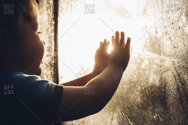 Toddler boy touching window