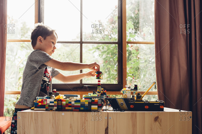 Boy playing with blocks by a window