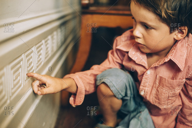 Little boy tracing trim pattern with his finger