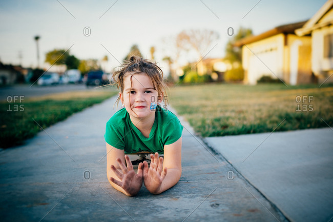 Girl on skateboard showing her dirty hands