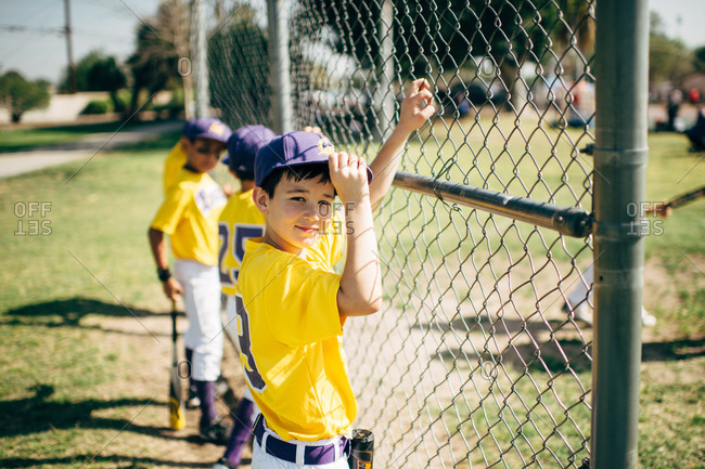 Boys on a baseball team standing by a fence