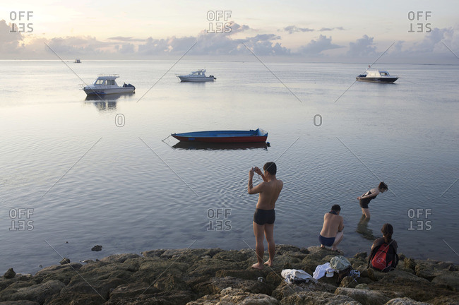 Bali, Indonesia - February 23, 2009: Man using a smartphone to take a photo at water's edge