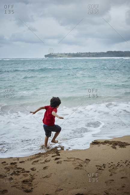 Young boy playing in waves at Hanalei Bay, Kauai
