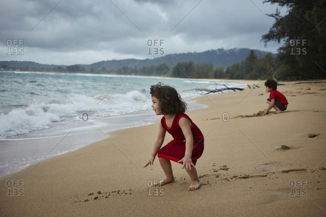 Kauai, Hawaii, USA - February 15, 2016: Young boy and girl waiting for the waves on beach at Hanalei Bay