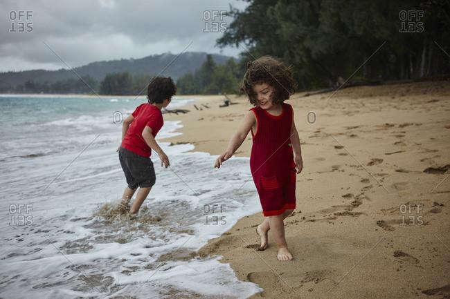 Kauai, Hawaii, USA - February 15, 2016: Two young children frolic on the beach in Hanalei Bay