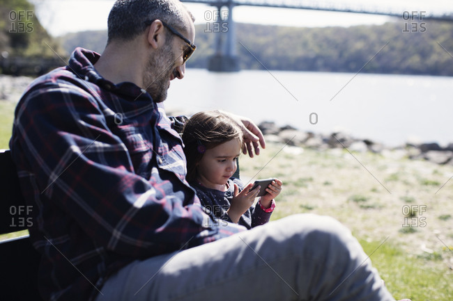 Father and daughter sitting on a bench outdoors together playing with a smartphone