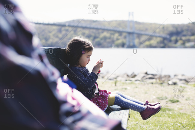 Young girl sitting on a bench outdoors playing with a smartphone