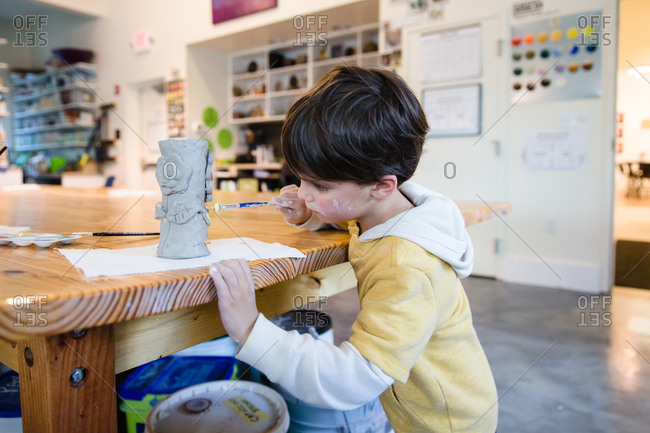 Boy painting a clay sculpture