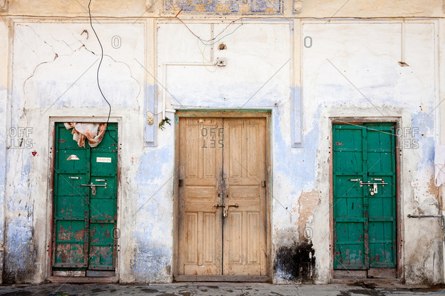 Green doors on either side of a wooden door on building in India
