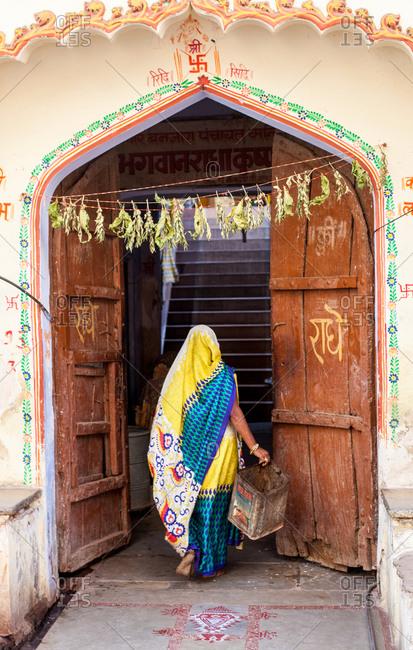 Back view of woman in colorful sari walking through a doorway