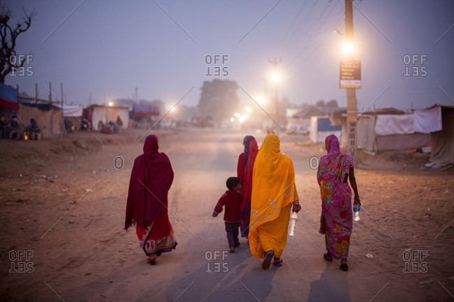 November 16, 2015: Four women and young boy walk on road at dusk in India