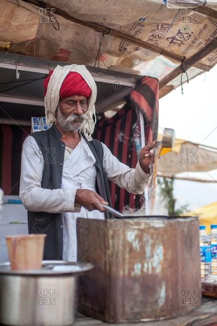 November 16, 2015: Indian man preparing food at outdoor food stall