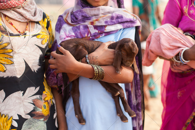 Woman with baby goat in her arms