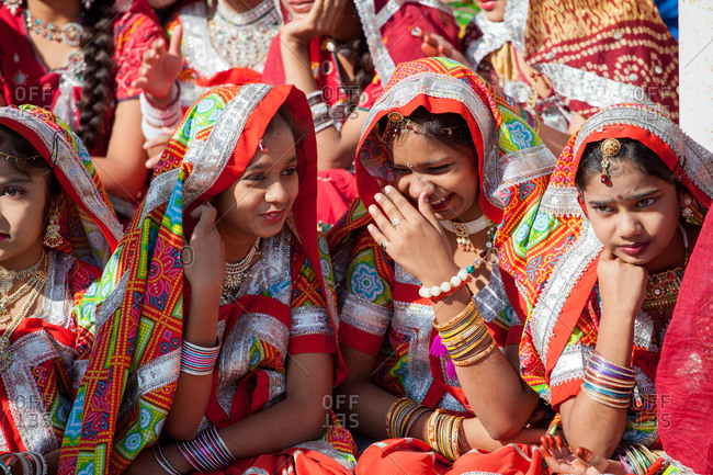 November 19, 2015: Young women in beautiful red saris laugh together, India
