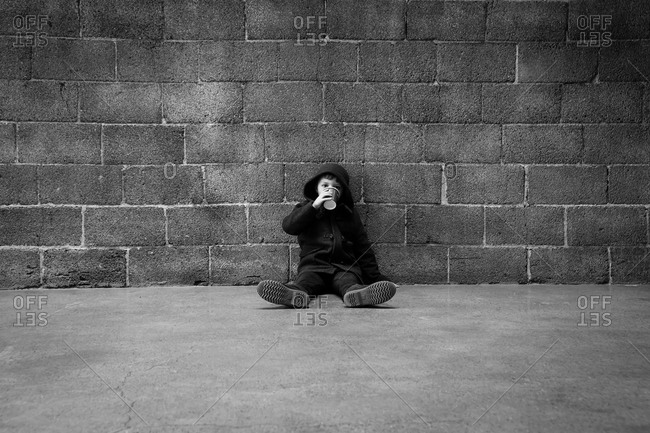 Boy wearing a coat and hood sitting against a brick wall and drinking