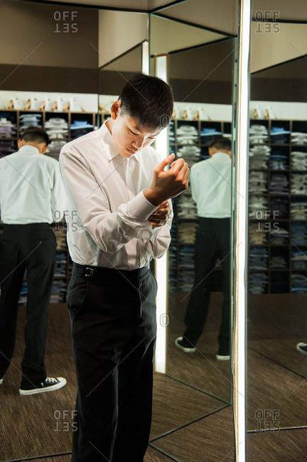 Teen boy buttoning the sleeve of a dress shirt