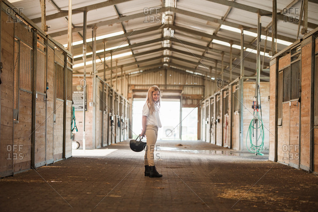 Girl standing in horse stables wearing riding gear