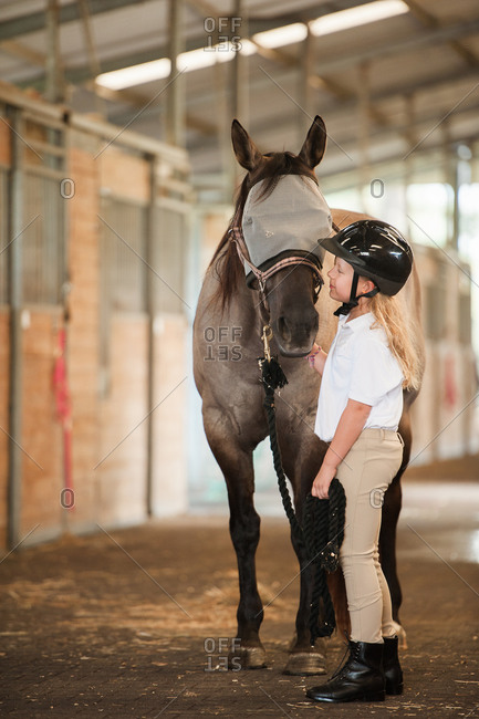 Girl in stables facing her horse