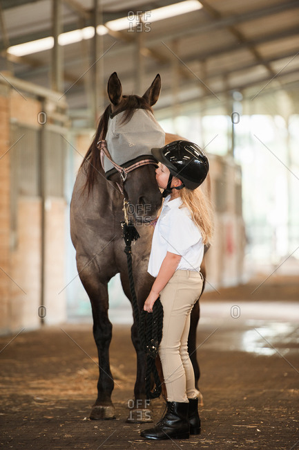 Girl standing in the middles of stables kissing her horse