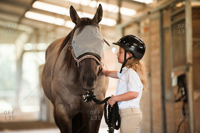 Girl in stables standing next to her horse