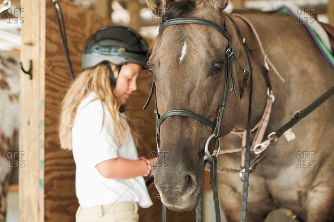 Girl in a stall preparing her horse for a ride