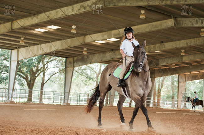 Girl riding her horse for practice in an equestrian arena