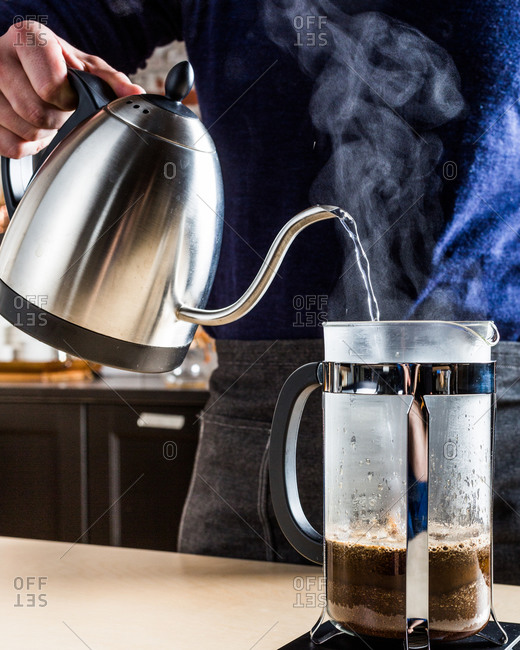 A person using a gooseneck kettle for a French press coffee