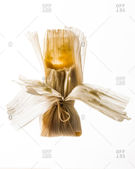 Partially opened tamale on a white background