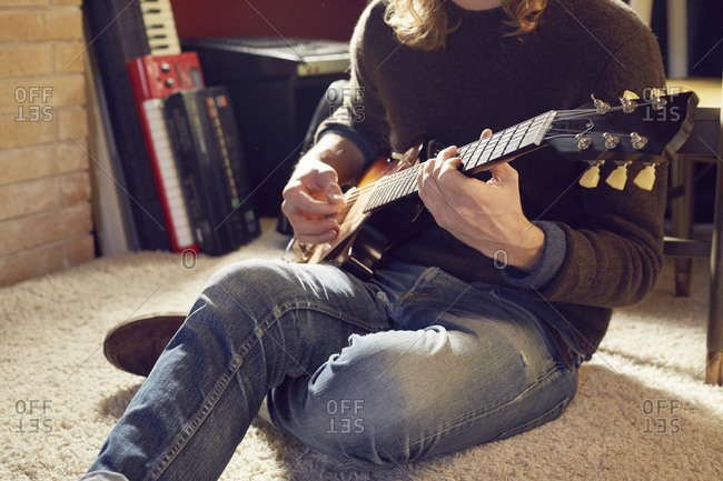 Young man sitting on a floor playing a guitar