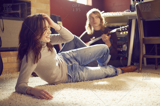 Young woman relaxing on a carpet while her boyfriend plays guitar