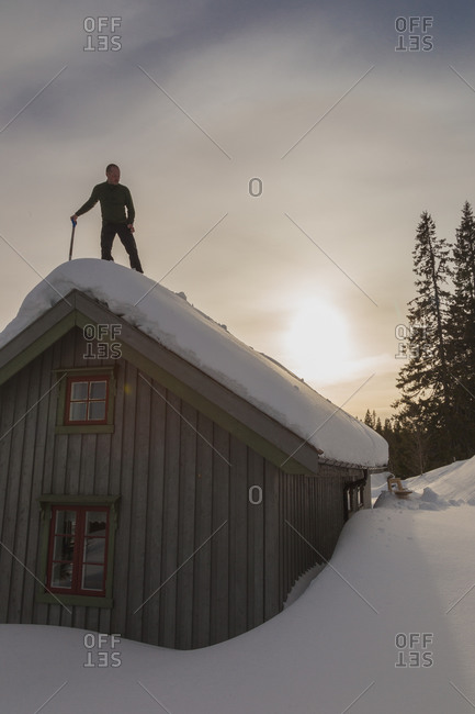 Man on roof with snow shovel