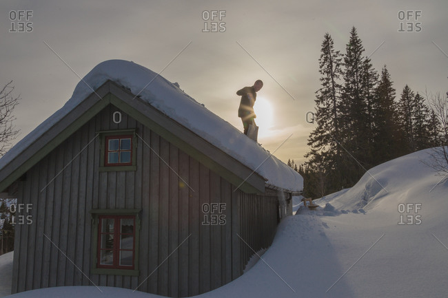 Man on snowy roof with shovel