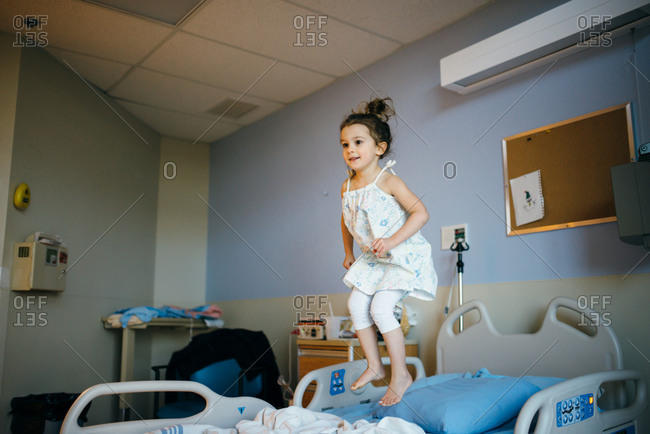 Little girl jumping on a hospital bed