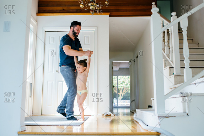 Father dancing with his daughter in the entryway