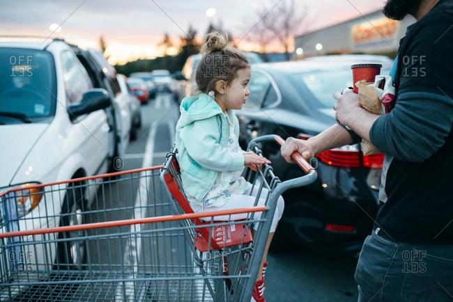 Man pushing girl in shopping cart