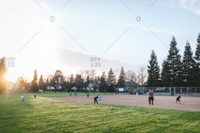 Kids' baseball team practicing on a field at sunset