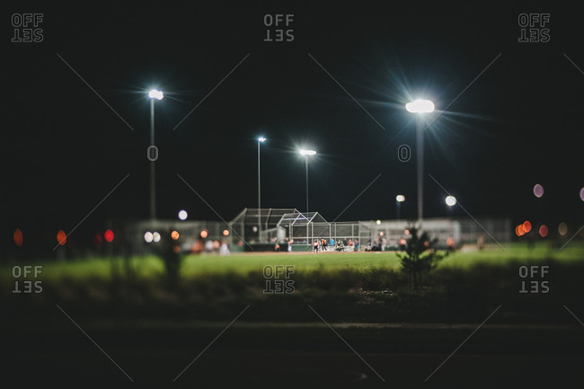 Baseball field and players lit up at night
