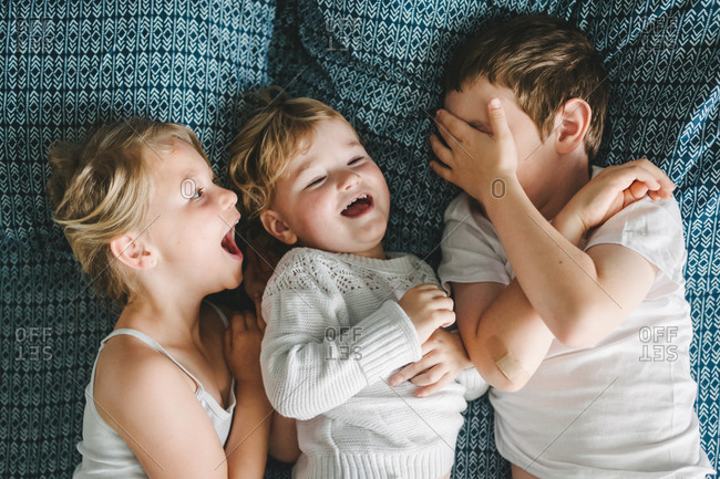Three siblings lying on a bed smiling and laughing