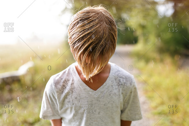 A young boy standing outside in the rain with his head down