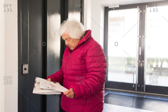 Elderly woman waiting in front of elevator holding mail
