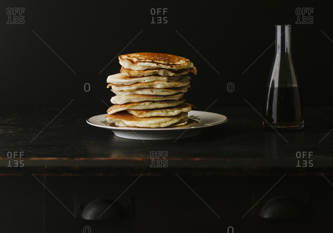 Stack of pancakes on rustic wooden table with local maple syrup