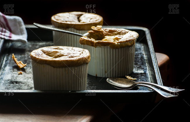 Miniature chicken pot pies, ready to serve with spoons and napkin