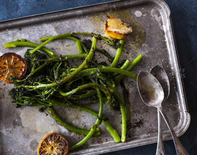 Seared broccolini on a rustic baking sheet with grilled lemons and serving spoons