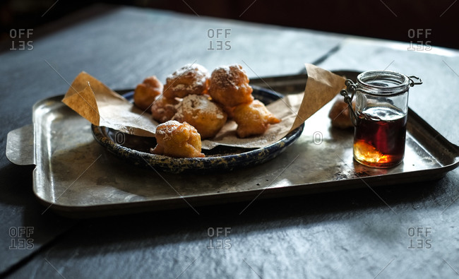 Apple fritters covered with powdered sugar and jar of honey