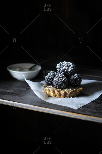Miniature blackberry tart with a small bowl of whipped cream