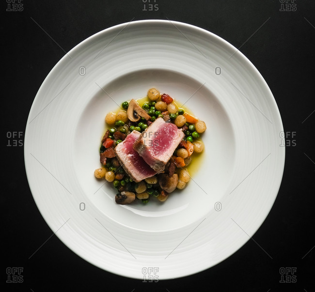 Seared ahi tuna with peas, mushrooms and gnocchi in a white bowl
