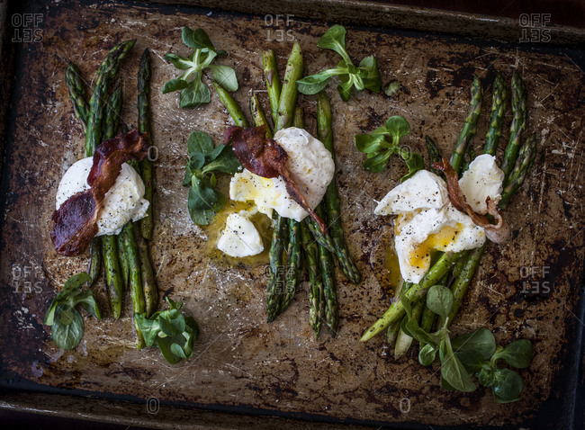Three poached eggs with grilled asparagus, mache and crisp bacon on a sheet pan