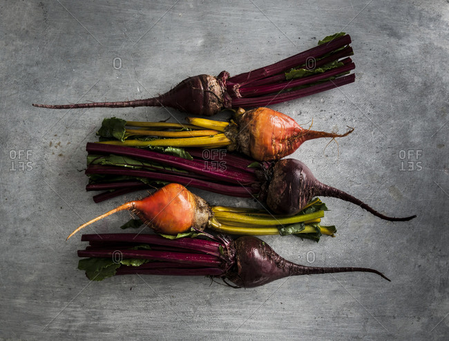 Trimmed red and gold beets on a rustic, scratched pan